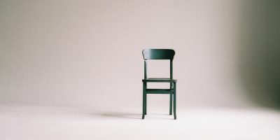 green chair in front of empty wall